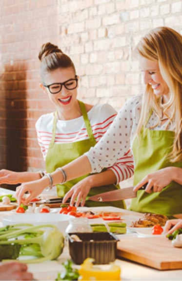 Two women cooking and laughing