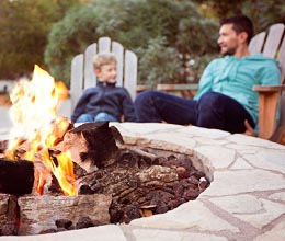Father and son sitting by fire pit