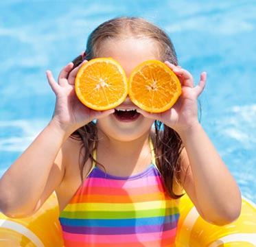 Girl holding up orange slices covering her eyes