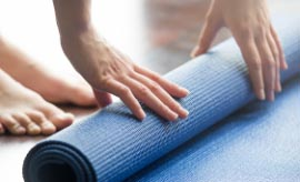 Close up of woman rolling up yoga mat