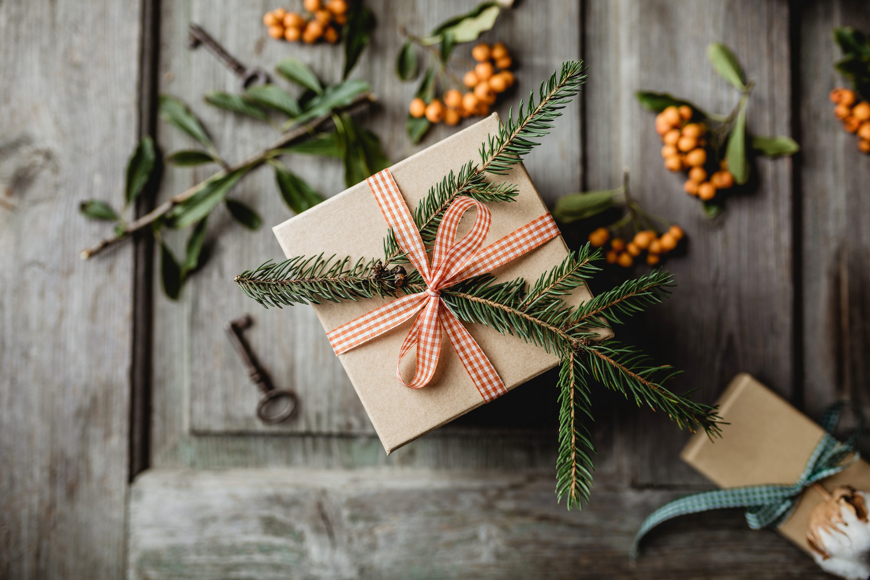 a gift wrapped and covered in pine tree clippings